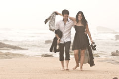 Young romantic couple walking along beach. After a night out Royalty Free Stock Images