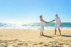 Young romantic couple walking on the beach holding hands Stock Photography