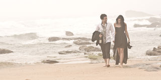 Young romantic couple walking long beach. Through the mist Royalty Free Stock Image