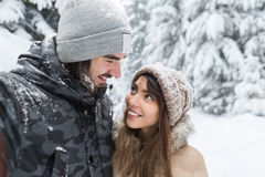 Young Romantic Couple Walking In Snow Forest Outdoor Mix Race Man And Woman Embrace. Winter Pine Woods Royalty Free Stock Photo