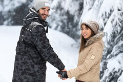 Young Romantic Couple Walking In Snow Forest Outdoor Mix Race man And Woman Holding Hands Royalty Free Stock Images