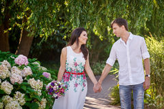 Young romantic couple walking in the summer park Royalty Free Stock Photos