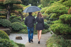 Young romantic couple walking together in park with umbrella. Young romantic couple holding hands walking together under umbrella outside in the park, view from royalty free stock photos