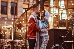 A young romantic couple wearing warm clothes hugging outdoor in evening street at Christmas time, enjoying spending time. A young romantic couple wearing warm royalty free stock image