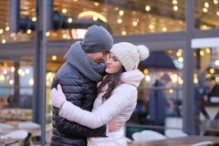 A young romantic couple wearing warm clothes hugging together in evening street near a cafe outside at Christmas time. Happy romantic couple wearing warm clothes stock photography