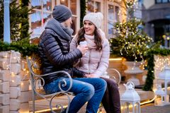 Romantic couple wearing warm clothes sitting on a bench in evening street decorated with beautiful lights, talking and. A young romantic couple wearing warm royalty free stock image
