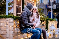Romantic couple wearing warm clothes sitting on a bench in evening street decorated with beautiful lights, talking and. A young romantic couple wearing warm royalty free stock images