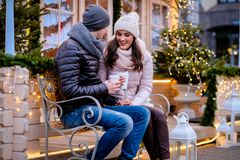 Romantic couple wearing warm clothes sitting on a bench in evening street decorated with beautiful lights, talking and. A young romantic couple wearing warm royalty free stock photos