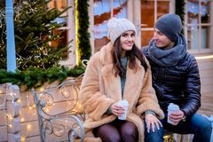 A young romantic couple wearing warm clothes sitting on a bench in evening street decorated with beautiful lights royalty free stock photography