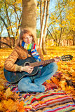 Young romantic girl in autumn park with guitar Royalty Free Stock Images
