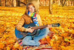 Young romantic girl in autumn park with guitar. Young romantic girl sitting in autumn park with guitar Stock Photos