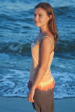 Young romantic girl on beach at sunset Stock Image