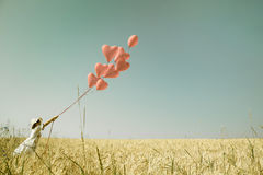 Young romantic girl with red heart balloons walking in a field o Royalty Free Stock Images