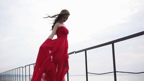 Beautiful woman in long red dress is standing on a sea pier in windy weather stock video