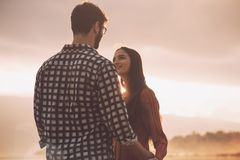 Young loving couple holding hands at sunset stock photos