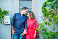 Young romantic married couple in bright clothes standing near their new home house door. Outdoor view of blue house wall with post. Box and green plants around Royalty Free Stock Photography