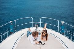 Attractive couple on the yacht. Young man is taking photo of his girlfriend royalty free stock images
