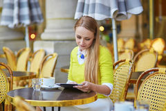 Young romantic Parisian girl in an outdoor cafe using tablet Royalty Free Stock Photos