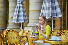 Young romantic Parisian girl in an outdoor cafe using tablet Royalty Free Stock Images