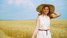 Young woman in white dress and straw hat walking on wheat field in summer. Young romantic red haired woman in white cotton dress and big straw hat walking on stock footage