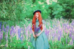 Young romantic redhead girl with very long hair on lupine background. Fabulous renaissance woman in mint dress against backdrop of. Beautiful flowers. Spring stock image