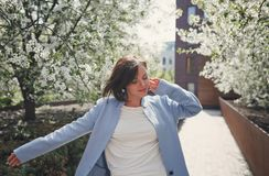 A young pretty smiling brunette woman with short hair in a blue summer coat dances in a blossoming park with cherry trees. royalty free stock photo