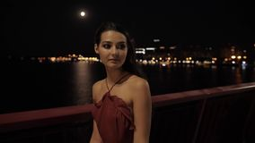 Beautiful tourist woman in night city. Young romantic tourist woman walking over the bridge against ligths of night city background. beautiful young mixed race stock footage
