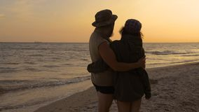 Young romantic travelers looking to the beach sky, enjoying sunset at the sea - love, summer and travel concept. stock video footage