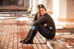 Young romantic woman in black sweater sitting on street Stock Photos