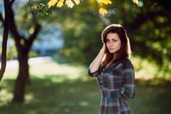 Young romantic woman in long checkered blue dress over background autumn portrait. Pretty girl posing in park with cup of coffe. F Stock Photo