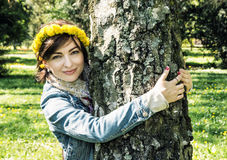 Young romantic woman with wreath of dandelions on the head is hu Royalty Free Stock Photography