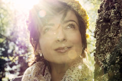 Young romantic woman with wreath of dandelions on the head in su Royalty Free Stock Images