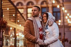 A young romantic couple wearing warm clothes hugging outdoor in evening street at Christmas time, enjoying spending time. A young romantiouple wearing warm stock image