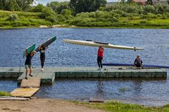 Young rowers take kayaks off water after training, Polotsk, Bela Stock Photos