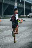 Young runner of Asian appearance looking back at rivals Royalty Free Stock Photography
