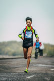 Young runner of Asian appearance running along river Royalty Free Stock Photography