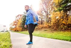 Young runner in autumn park standing on concrete path. Stock Photos