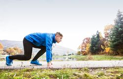 Runner at the lake on asphalt path in steady position. Royalty Free Stock Photography