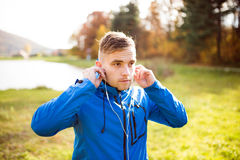 Young runner with earphones outside in sunny autumn nature Royalty Free Stock Photos