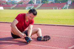 Young runner having pain at joint between running. Young asian runner having pain at joint between running in stadium stock images