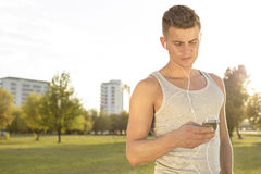 Young runner listening to music through cell phone in park Royalty Free Stock Photo