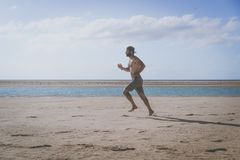 Young runner running in morning along the beach. Young runner running in morning along the beach Stock Photo