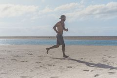 Young runner running in morning along the beach. Young bearded man jogging on the sea shore at sunrise. Young runner running in morning along the beach. Young Royalty Free Stock Images