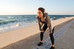 Young runner woman resting after workout with hands on her knees. Seaside outdoor royalty free stock photo