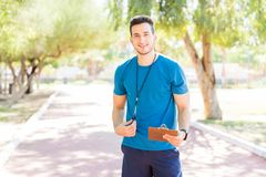 Running Coach Holding Clipboard And Whistle On Footpath In Park. Young running coach holding clipboard and whistle while standing on footpath in park stock photos