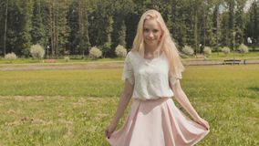 A young Russian girl blonde posing in a city park on a summer day. stock video