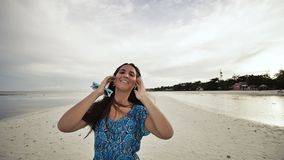 A young Russian girl with happy emotions is walking along the beach and posing in front of the camera. The girl is stock video
