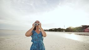 A young Russian girl with happy emotions is walking along the beach and posing in front of the camera. The girl is stock footage