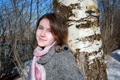 Young Russian woman next to a birch. Young russian woman standing next to a birch tree smiling in the spring sun Stock Images