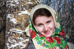Young Russian woman in a scarf. Young russian woman wearing traditional scarf standing next to a birch tree in spring Stock Images